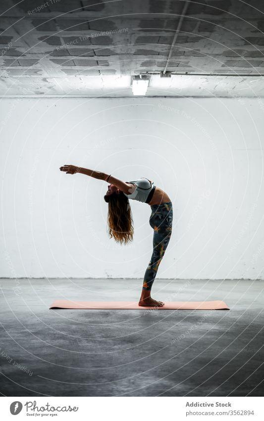 Schlanke Frau macht Yoga in Berg-Pose mit erhobenem Arm Gleichgewicht üben Windstille Stehende Rückbeuge schlanke Asana Unterlage beweglich stehen Stock