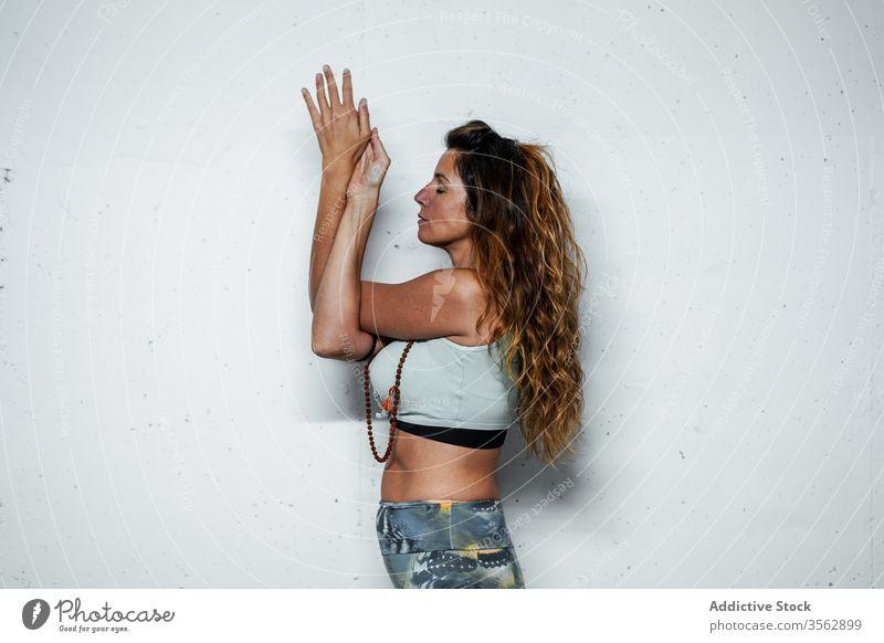 Ruhige Frau macht Yoga in Adler-Pose meditieren üben garudasana Achtsamkeit Gelassenheit ruhig Harmonie Gleichgewicht Windstille Mudra beweglich schlanke Asana
