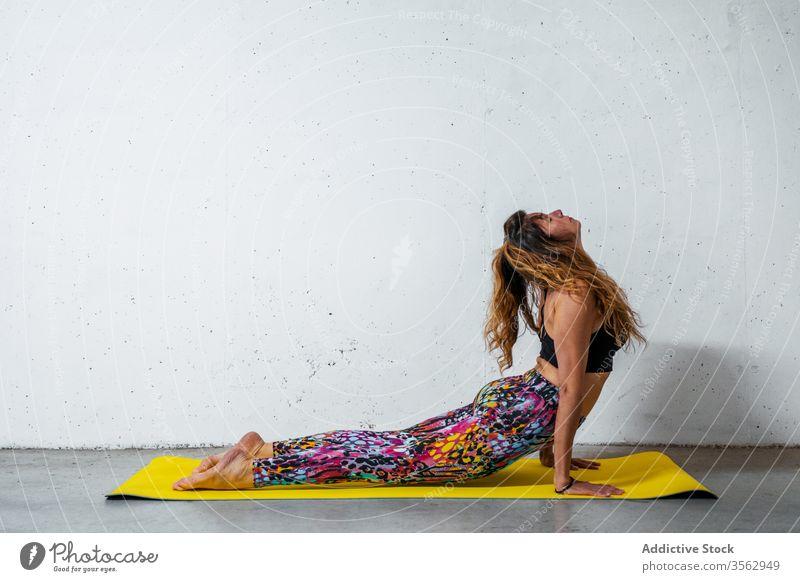 Frau praktiziert Yoga auf der Matte üben nach oben gerichtete Hundehaltung bhujangasana Unterlage Körperhaltung positionieren Gleichgewicht Augen geschlossen