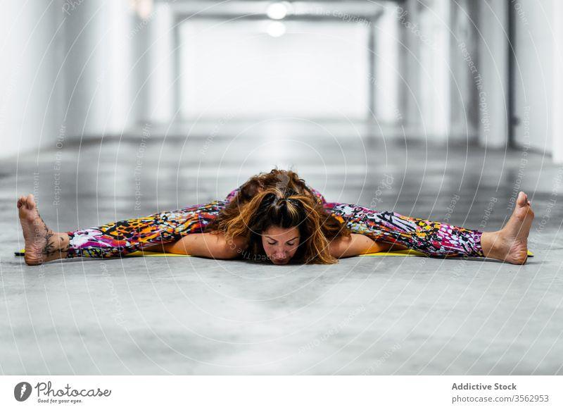 Junge Frau, die Yoga in sitzender Vorbeugeposition praktiziert üben Asana weitergeben Wegbiegung Garage Pose upavistha konasana positionieren fortgeschritten