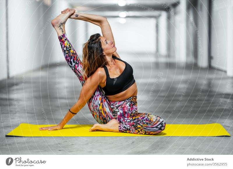 Frau dehnt Körper in Yogastellung üben Dehnung Kompass Asana Pose Garage positionieren parivrita surya yantrasana beweglich fortgeschritten Herausforderung