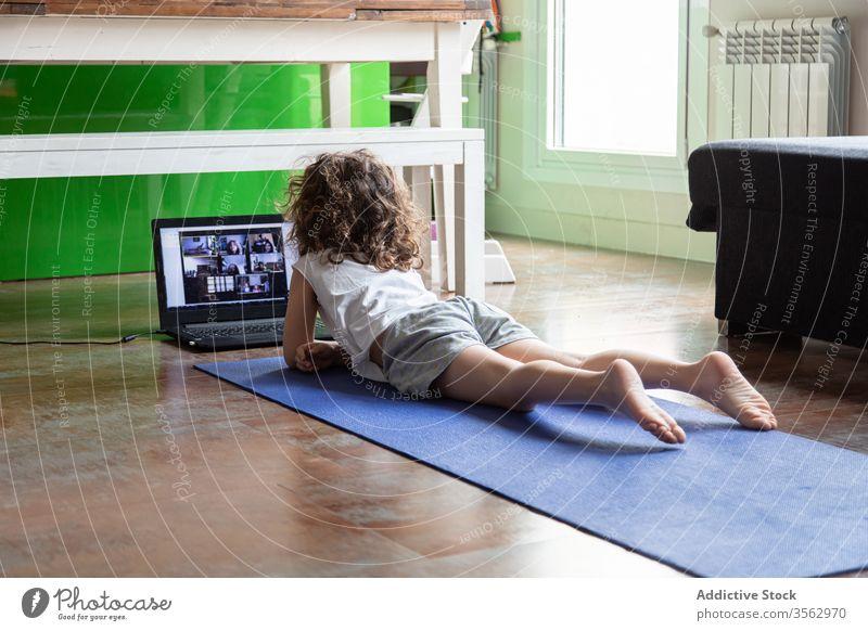 Kleines Mädchen lernt zu Hause online Yoga Kind Laptop üben heimwärts zuschauen Video Tutorial lernen Pose Gerät Apparatur Internet benutzend Unterlage wenig
