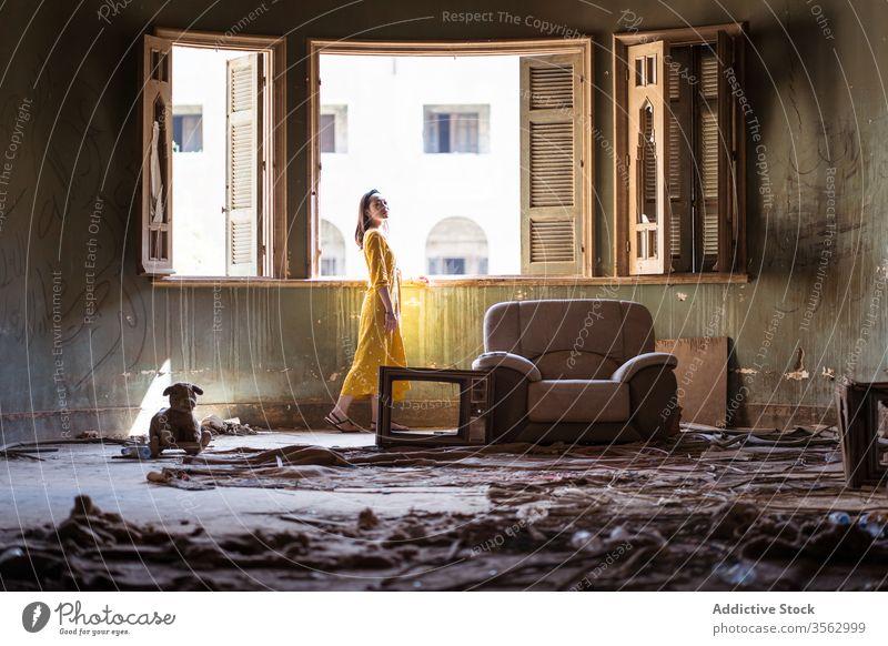 Frau steht im Wohnzimmer eines verlassenen Hauses Fenster Raum Verlassen Unbewohnt alt schäbig unordentlich Appartement wohnbedingt jung ethnisch Saudi-Arabien