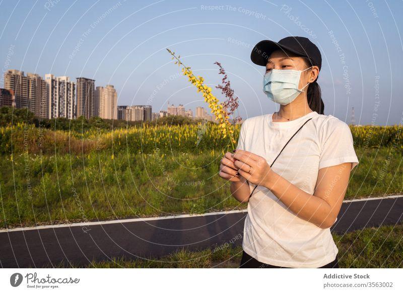 Ethnische Frau mit medizinischer Maske steht auf grünem Feld Mundschutz behüten Coronavirus verhindern COVID Natur jung lässig ethnisch modern Sicherheit