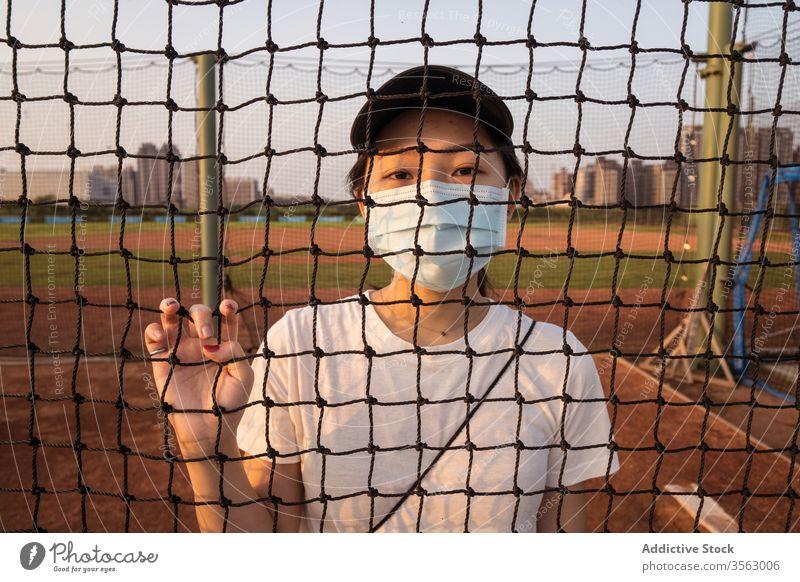 Junge Frau mit Schutzmaske steht hinter Netzzaun auf Sportplatz Mundschutz Coronavirus Sportpark Zaun Einschränkung verhindern behüten COVID jung sportlich