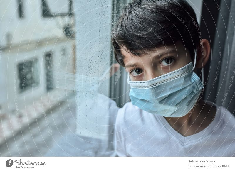 Trauriger Junge mit medizinischer Maske am Fenster Mundschutz Coronavirus Seuche heimwärts traurig unglücklich Selbstisolierung soziale Distanzierung Kind
