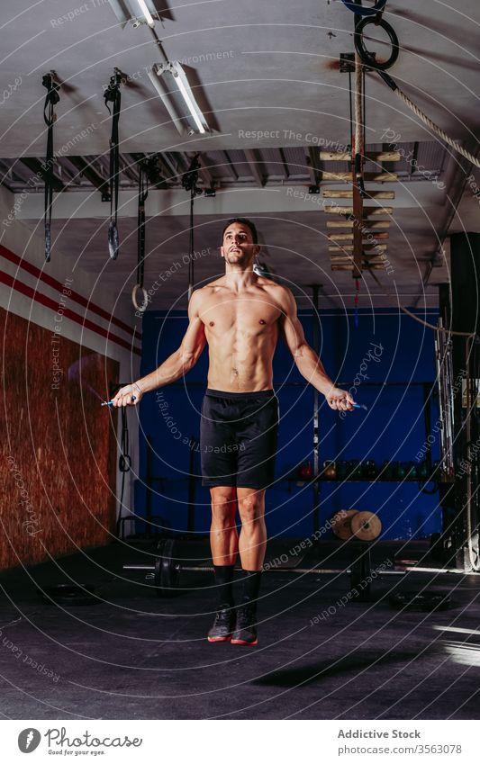 Fitnesssportler beim Training mit Springseil Sportler Hüpfseil Übung überspringen Seil passen aktiv Ausdauer nackter Torso männlich muskulös stark Fitnessstudio