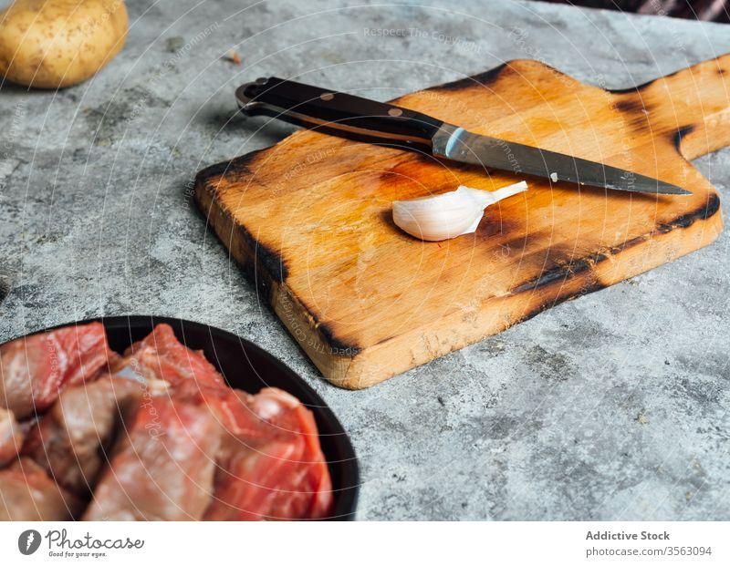 Knoblauchzehe auf dem Schneidebrett in der Küche Gewürznelke Messer frisch Fleisch Tisch roh Schalen & Schüsseln Rindfleisch Lebensmittel ungekocht vorbereiten