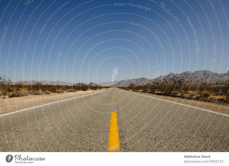 Leere Autobahn auf felsiger Landschaft Straße Autoreise Route wüst Asphalt Sand trocknen erwärmen Berge u. Gebirge malerisch Natur Ausflug Tal Windstille
