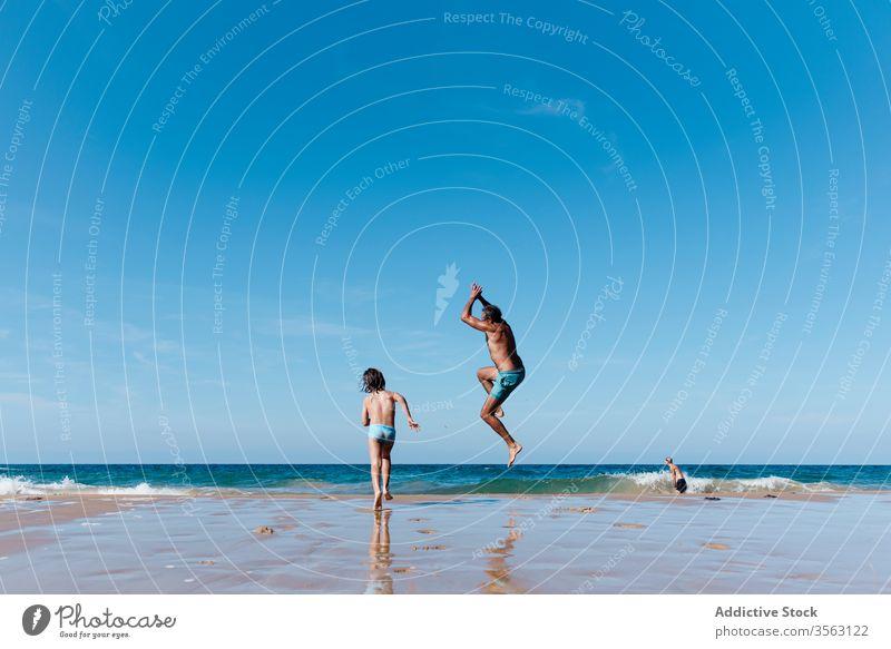 Vater und Kind haben Spaß am Strand MEER Spaß haben springen Zusammensein Glück Urlaub Feiertag Mann Wasser Sommer laufen Sand Meer Küste Ufer Freude Natur
