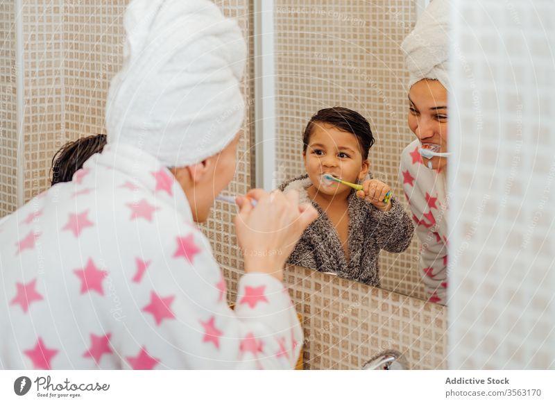 Fröhlicher Sohn und Mutter mit Zahnbürste im Badezimmer Bürste Zähne Junge Bademantel mündlich Hygiene Lächeln wenig Kind Mama Elternschaft Gesundheit Spiegel