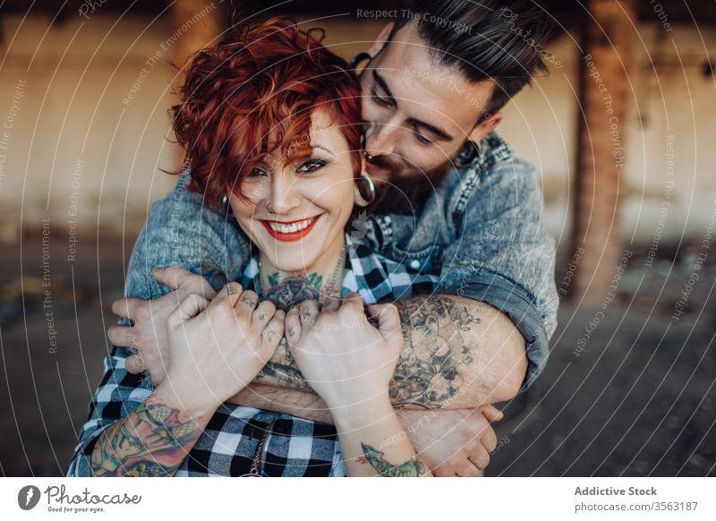 Glückliches junges Paar umarmt fast verwittertes Gebäude Liebe Umarmen Hipster Straße schäbig Zusammensein Umarmung Partnerschaft Tattoo Freund Freundin