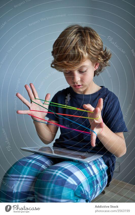 Kind mit Tablette lernt Katzenwiege-Spiel Schnur spielen lernen Wiege Kreativität Figur Hocker Pyjama heimwärts Junge Fokus Krawatte Vorstellungskraft Fähigkeit