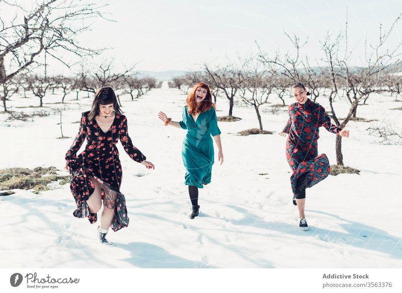 Fröhliche modische Frauen laufen auf Schnee Zusammensein Glück Spaß Winter Feld Freund heiter trendy Natur Mode Stil jung Freude Lächeln sich[Akk] entspannen