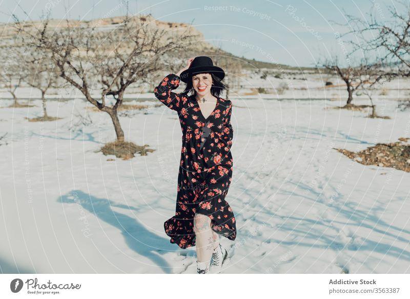 Selbstbewusste trendige Frau steht im verschneiten Feld Stil trendy selbstbewusst Schnee Natur attraktiv in die Kamera schauen modern Mode charmant farbenfroh
