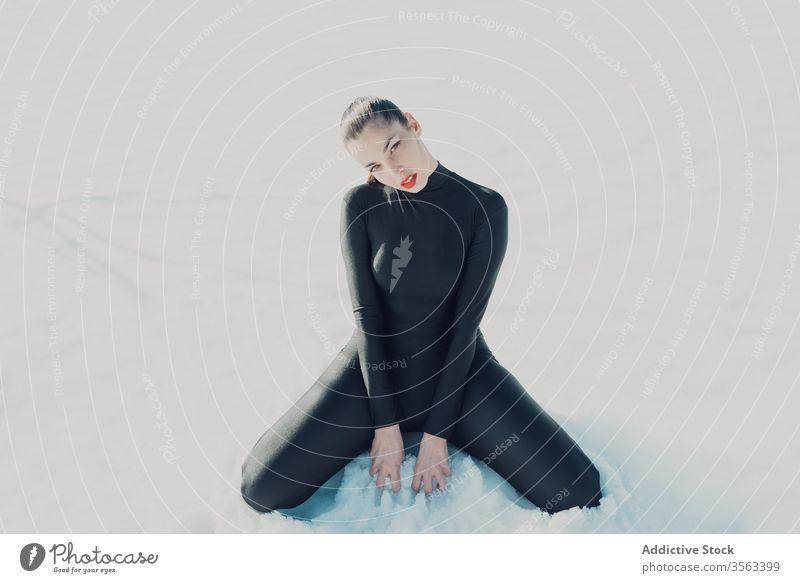 Sinnliche Frau im schwarzen Anzug sitzt auf Schnee sinnlich verführerisch Leidenschaft jung attraktiv Körper sexy schlank rote Lippen Dame trendy Versuchung