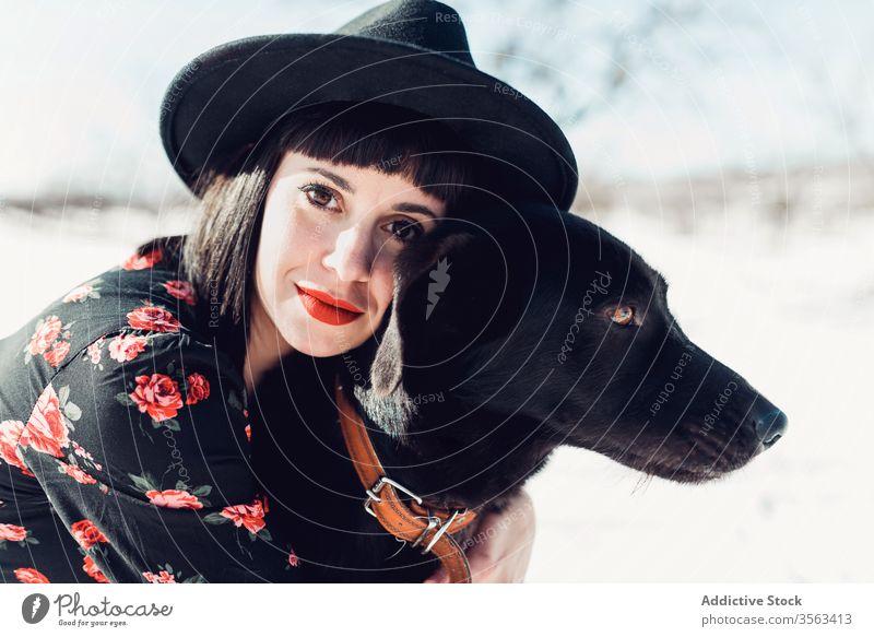 Stilvolle Frau mit Hund im Winterfeld Feld trendy Schnee schwarz Zusammensein Haustier Mode Park sich[Akk] entspannen Wald Baum Windstille Hut züchten kalt