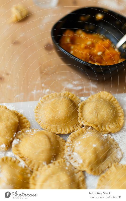 Rohe Ravioli auf dem Tisch in der Küche Schneidebrett rund kreisen besetzen Kürbis Püree Kochen Mehl roh Utensil vorbereiten Lebensmittel Italienisch