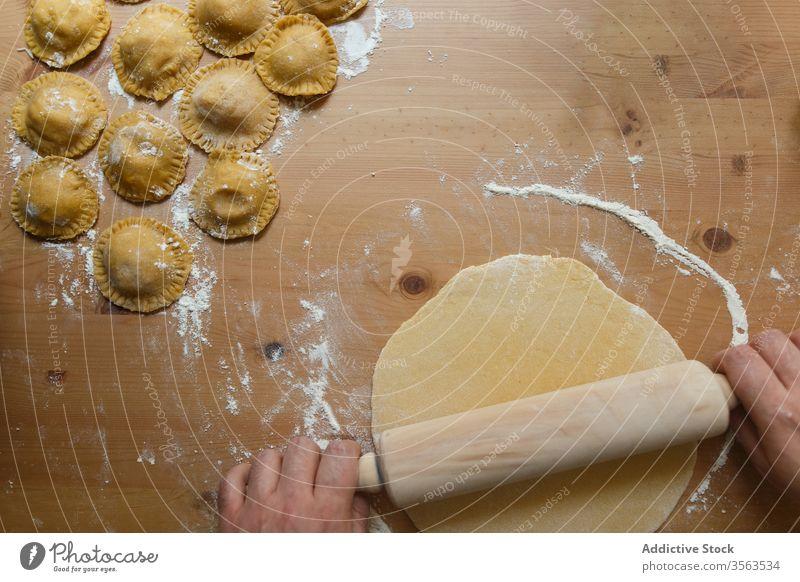 Männlicher Erntekoch rollt Teig mit Ravioli auf den Tisch Koch Nudelholz Teigwaren vorbereiten rollen kreisen roh Person rund hölzern Prozess Küche Lebensmittel