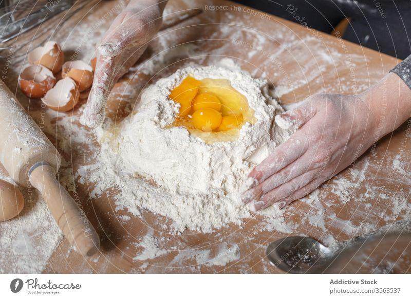 Pflanzenkoch bereitet Teig auf dem Tisch zu Koch Mehl hinzufügen Ei mischen Teigwaren Schulpause vorbereiten Lebensmittel Gebäck Gastronomie Küche Bestandteil
