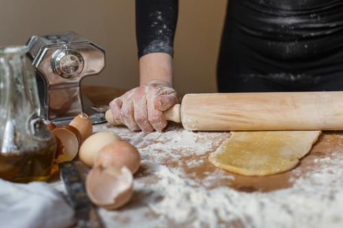 Crop Lady Teigrolle mit Nudelholz auf dem Tisch Koch Teigwaren Frau rollen Gebäck elastisch Mehl Ei Küchengeräte Kannen Eierschale Glas vorbereiten Bestandteil