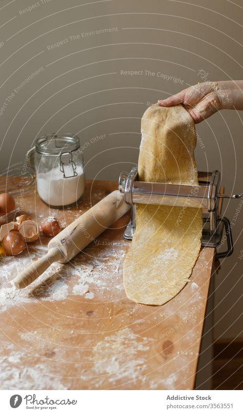 Anonyme Köchin rollt Teig aus, während sie die Nudelmaschine benutzt Frau Koch Spätzle rollen Maschine Teigwaren Gebäck elastisch Mehl Vorrichtung Küchengeräte