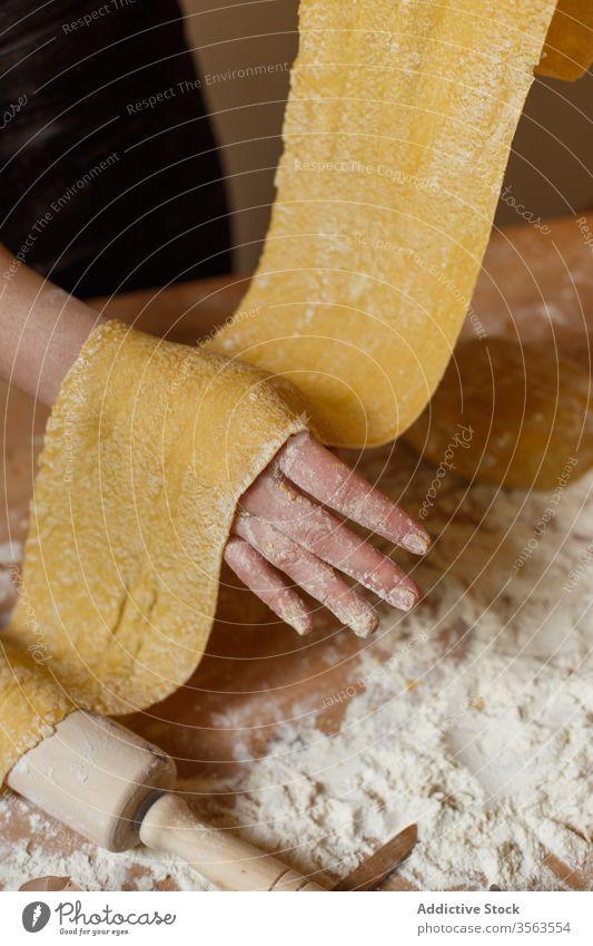 Gesichtslose Frau mit gerolltem Teig in der Küche Teigwaren elastisch Spätzle selbstgemacht Koch Mehl roh Küchengeräte rollen Speise Ei vorbereiten Bestandteil