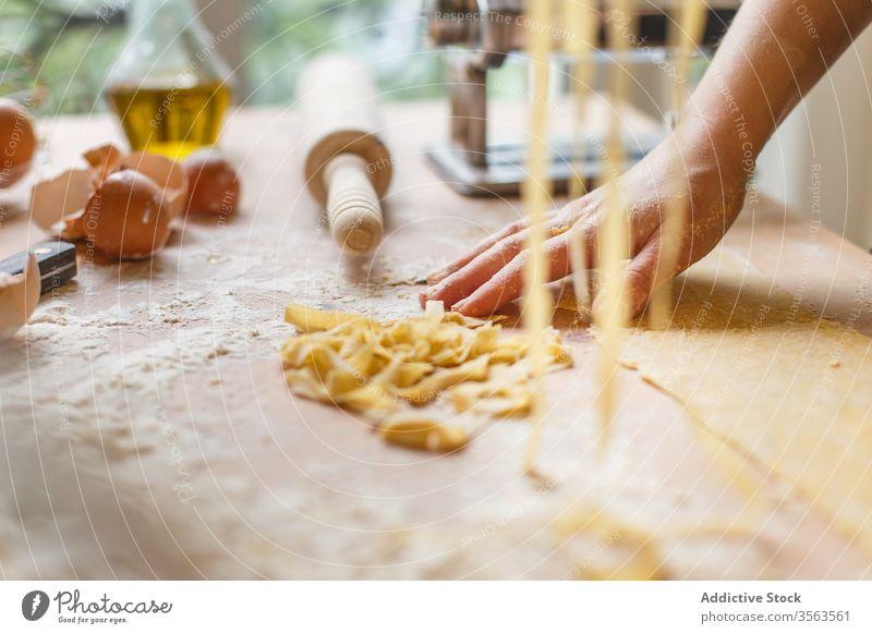 Nicht erkennbare Frau mit geschnittener roher Pasta Spätzle selbstgemacht Teigwaren Gurt dünn Streifen Gebäck Koch Tisch Mehl Küchengeräte rollen Eierschale