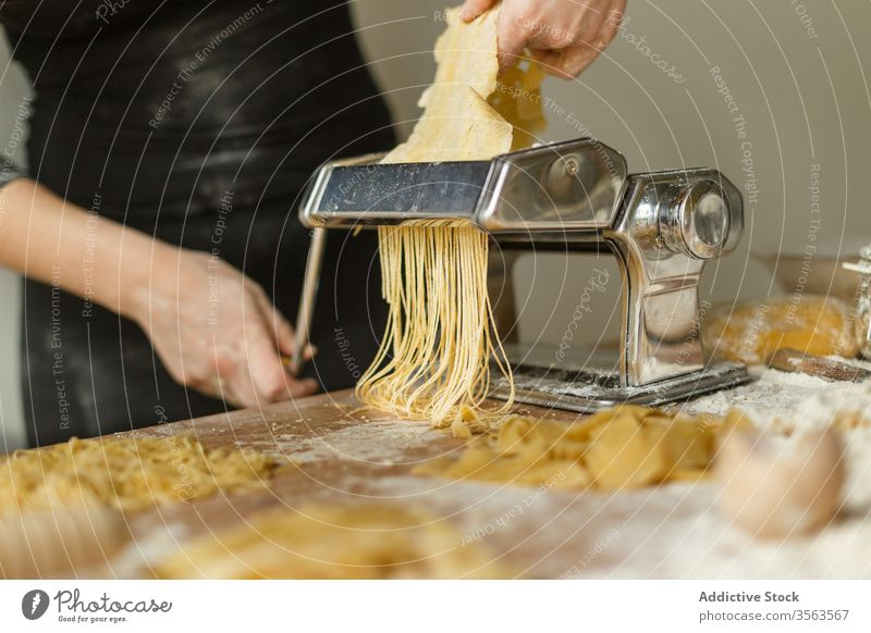 Gesichtslose Köchin schneidet Gebäck mit einer Nudelmaschine Frau Maschine Spätzle rollen Streifen geschnitten dünn benutzend roh Form Teigwaren Gerät Koch Mehl