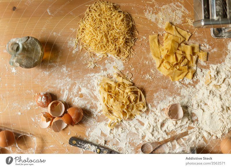 Zusammensetzung von Nudeln und Geschirr auf dem Tisch Spätzle roh Mehl Utensil Eierschale oliv Erdöl verschiedene Form Teigwaren Gebäck unordentlich machen