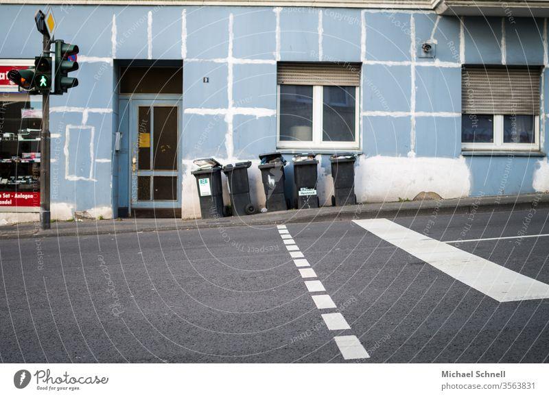 Fußgängerübergang mit Ampel hin zu einem unzureichend renoviertem Haus, mit Mülltonnen davor Übergang Architektur Straße Stadt Gebäude Verkehr Menschenleer