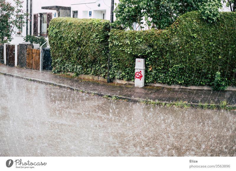 Eine Straße in einer Wohngegend bei starkem Regen Regenschauer leer nass schlechtes Wetter Herbst Bürgersteig Starkregen trist grau grün Sommerregen