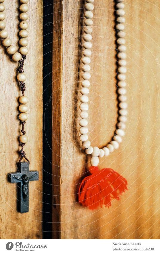 Katholischer Rosenkranz und Kruzifix, die an einer Tür hängen Christentum Religion Kirche altehrwürdig Perlen katholisch Glaube Gebet Holz Schnitzereien