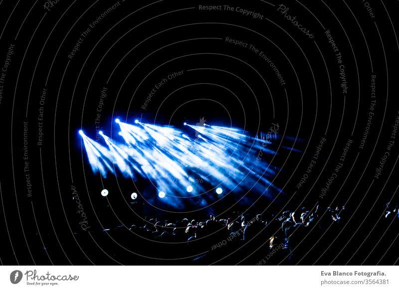Bild von vielen Menschen, die sich an nächtlichen Aufführungen erfreuen, große, nicht wiedererkennbare Menschenmenge, die mit erhobenen Händen und Mobiltelefonen im Konzert tanzt. Nachtleben