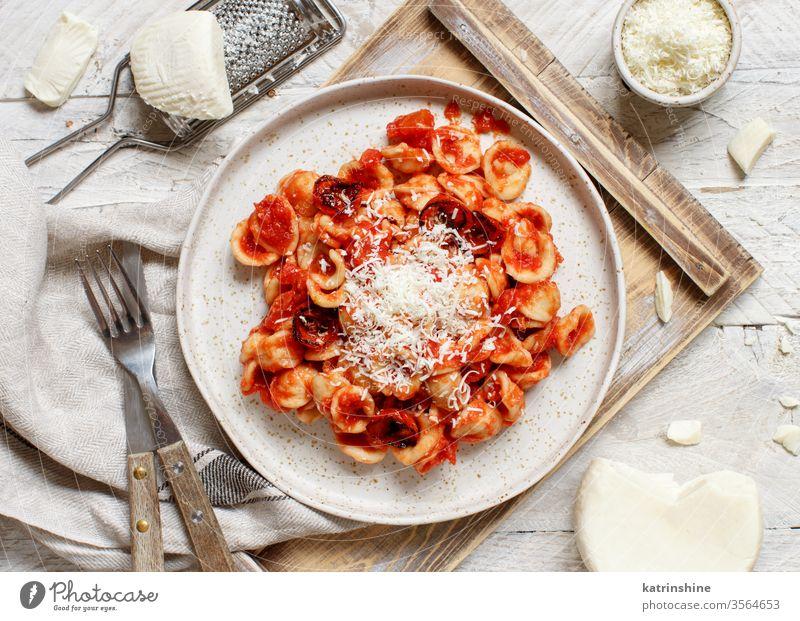 Süditalienische Pasta-Orecchiette mit Tomatensauce und Cacioricotta-Käse Spätzle Italienisch Apulien Saucen sugo Draufsicht Tablett weiß Reibeisen hölzern