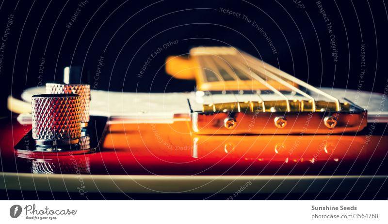 Nahaufnahme einer E-Gitarre mit Sonnenschlifflackierung Musikinstrument Stromgitarre altehrwürdig Holz Griffbrett Hals Schnur Kontrollen Knauf Instrument