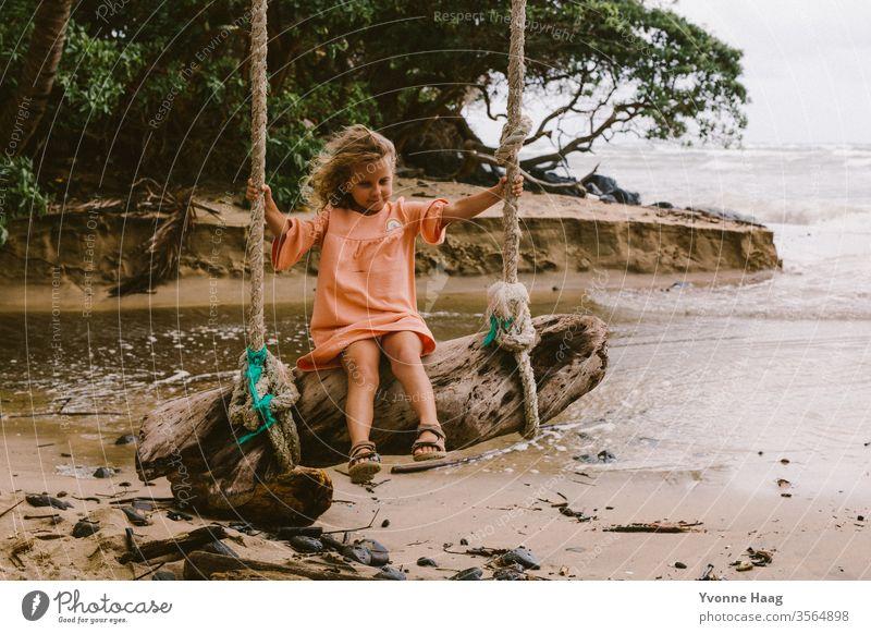 Auf einem großen Baumstamm schaukeln Hawaii Hawaiiblume Schaukelnd Freude Spielen Außenaufnahme Farbfoto Spielplatz Kindheit Tag Kinderspiel Textfreiraum rechts