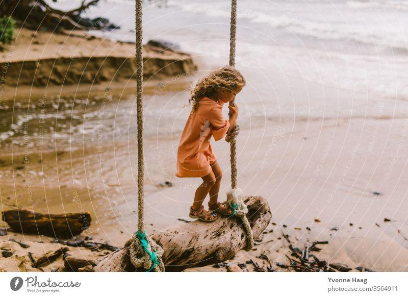 Mädchen steht auf einer Schaukel und schaukelt dem Meer entgegen Hawaii Hawaiiblume schaukeln Schaukelnd Freude Spielen Außenaufnahme Farbfoto Spielplatz
