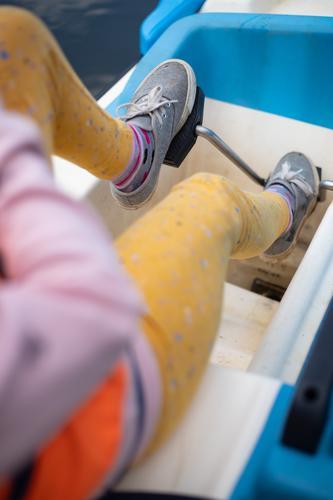 Tretboot fahren tretboot schiff füße wasser sport aktivität freizeit beine schuhe anstrengung anstrengend pedale kurbel see mädchen kind feminin makro