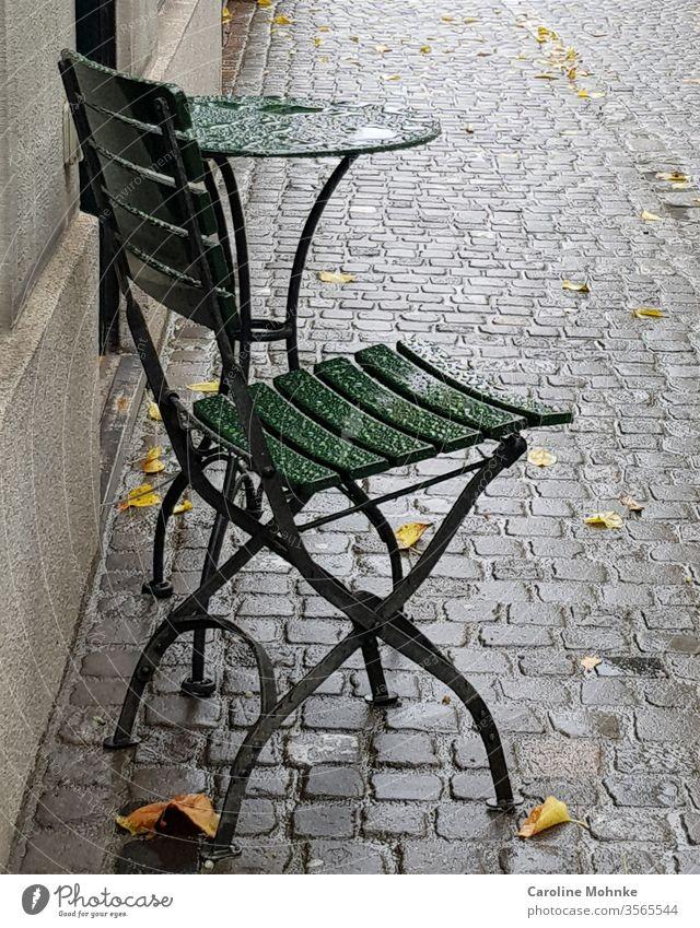Grüner Bistrostuhl und Tisch im Regen stehen gelassen tisch bistrostuhl bistrotisch Häusliches Leben Farbfoto Tag Menschenleer Außenaufnahme Möbel