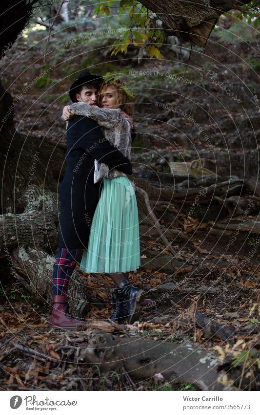Ein junges Boho-Paar umarmt sich in einem Waldhintergrund Freude Park Spaß Hirsche Freizeit hübsch cool stylisch Herbstlaub Kleid Romantik Land Partnerschaft