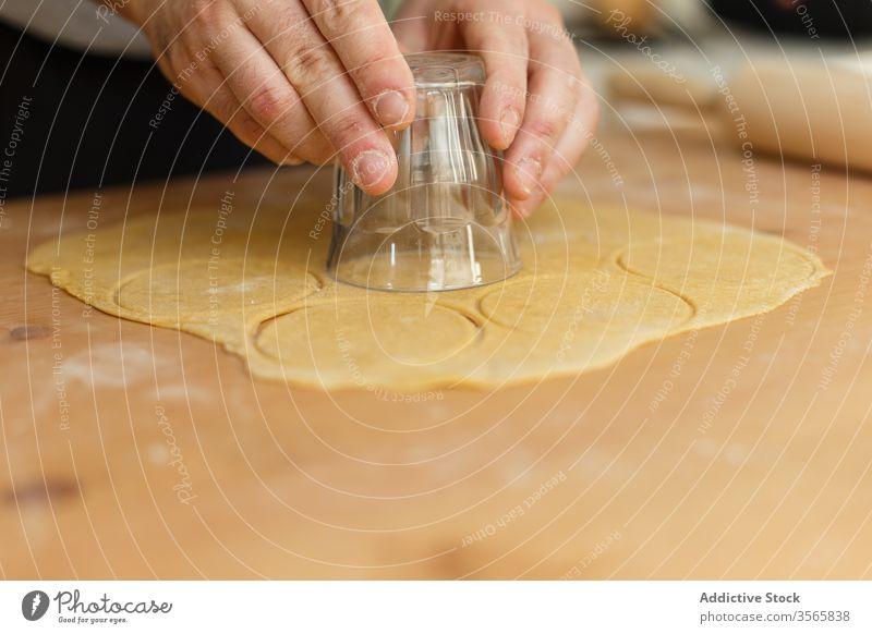 Anonymer männlicher Koch benutzt Glas zum Schneiden runder Formen für Ravioli Kutter Teigwaren Bestandteil Presse Nudelholz kreisen Tisch hölzern vorbereiten