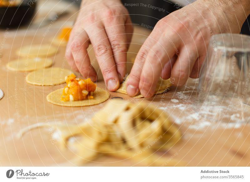 Erntehelfer, der Ravioli mit Kürbisfüllung füllt Teigwaren Zeug vorbereiten kreisen Koch Tisch rund hölzern Prozess Küche Lebensmittel kulinarisch selbstgemacht