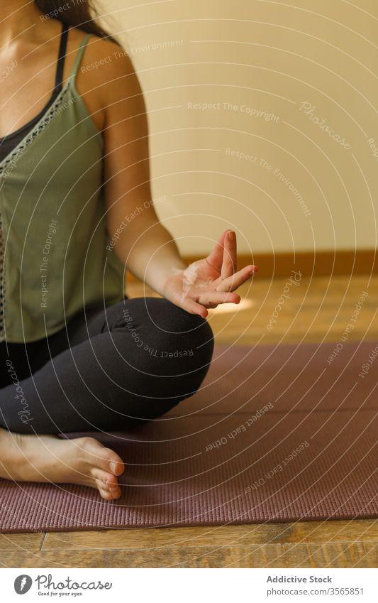 Nutzpflanzenfrau in Lotus-Pose auf Matte Yoga Mudra Frau gestikulieren Übung padmasana Sportbekleidung Unterlage Windstille üben Achtsamkeit stumm Gelassenheit
