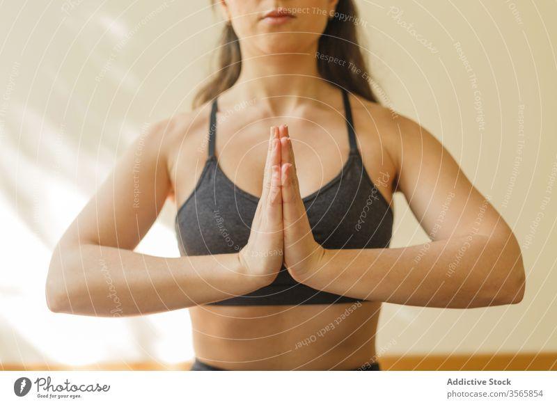 Ruhige Frau meditiert in Lotus-Pose meditieren Yoga Namaste padmasana Achtsamkeit ruhig Fokus heimwärts Konzentration Übung Unterlage Training Gelassenheit