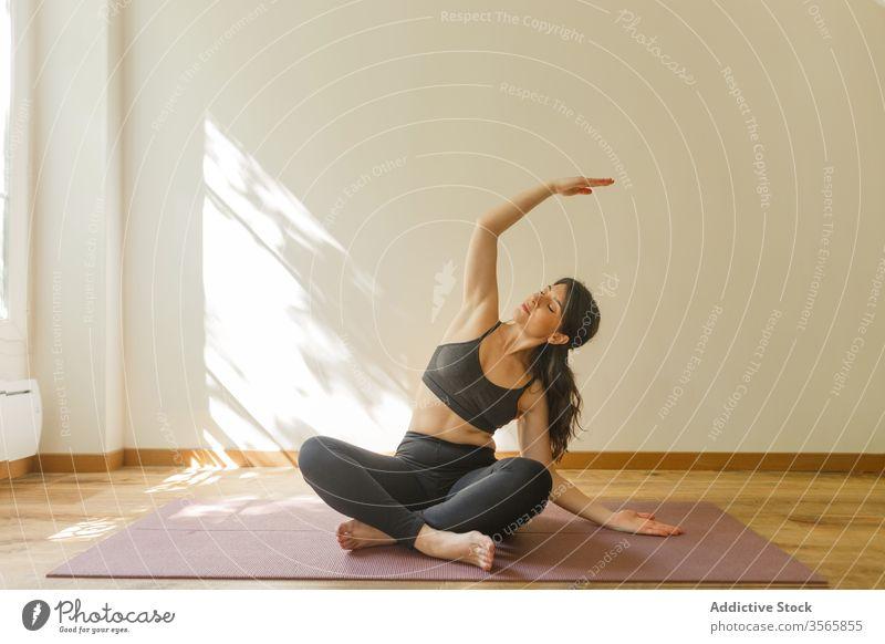 Flexible Frau macht Seitenbeuge und praktiziert Yoga Seitenknick üben Übung beweglich Achtsamkeit Gelassenheit sukhasana Wohnzimmer Dehnung heimwärts ruhig