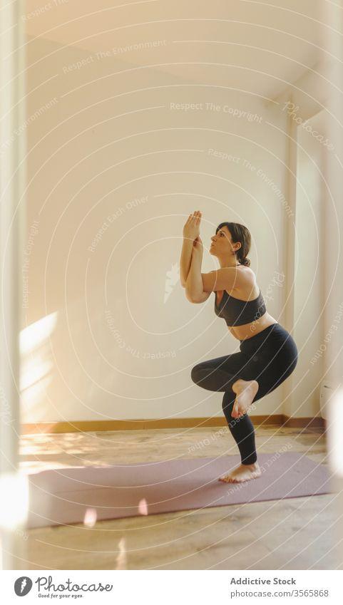 Sportlerin, die zu Hause in Adlerpose auf der Matte steht Frau Adler-Pose Yoga Gleichgewicht meditieren Gesunder Lebensstil Vitalität üben Wellness Unterlage