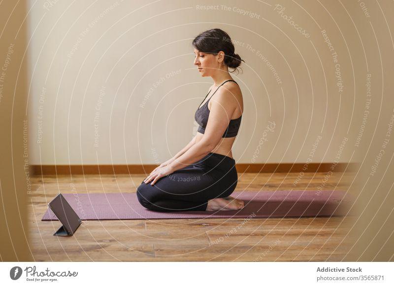 Frau nimmt Tablette während der Pause von der Yogapraxis zu Hause heimwärts üben Unterlage Tutorial ruhen online Touchscreen Sportbekleidung Gesunder Lebensstil