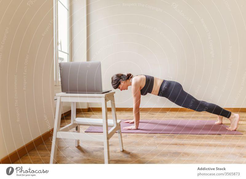 Passgenaue Frau, die zu Hause in Plankenpose steht Plankenhaltung Yoga üben Wellness heimwärts Gesunder Lebensstil Fitness Laptop Unterlage benutzend Gerät