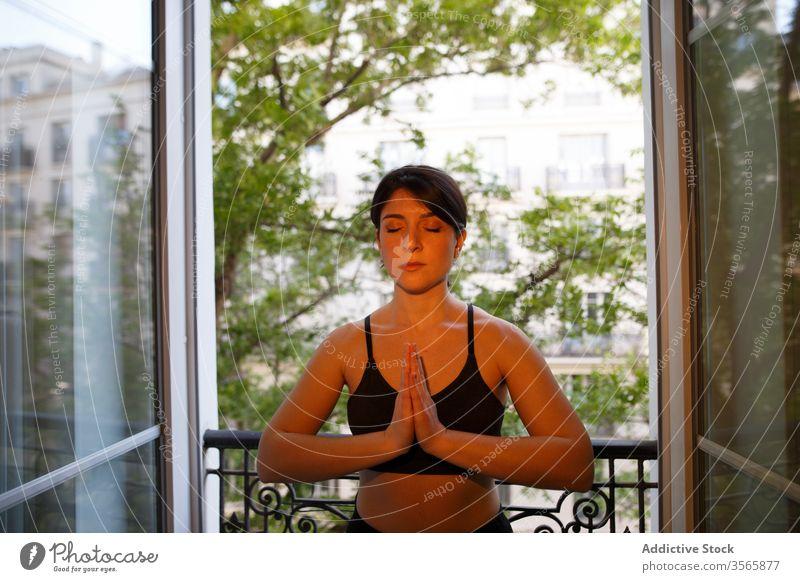 Ruhiges Stehen in Gebetspose auf dem Balkon im Sommer Frau Gebetshaltung Yoga Frieden Harmonie heimwärts sich[Akk] entspannen Augen geschlossen